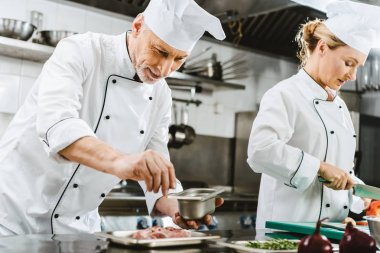 focused male and female chefs in uniform preparing food in restaurant kitchen