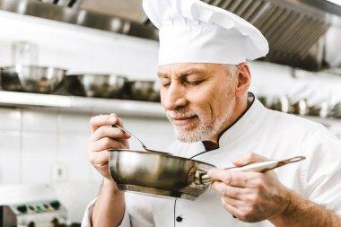 handsome male chef in uniform sniffing dish in pan in restaurant kitchen
