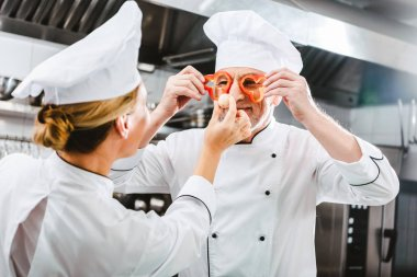 female cook looking at male chef holding pepper slices in front of face in restaurant kitchen