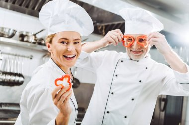 happy female cook looking at camera while male chef holding pepper slices in front of face in restaurant kitchen