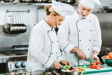smiling female and male chefs in uniform cutting ingredients while cooking in restaurant kitchen