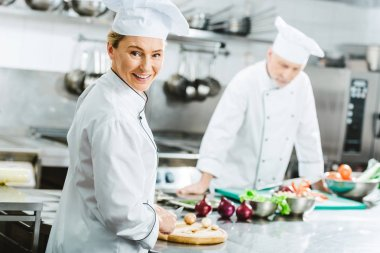 beautiful female chef looking at camera and smiling while cooking with colleague in restaurant kitchen