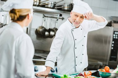 Selective focus of male and female chefs in uniform looking at each other while cooking food in restaurant kitchen stock vector