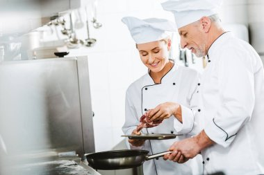 female and male chefs in uniform cooking meat on pan in restaurant kitchen with copy space