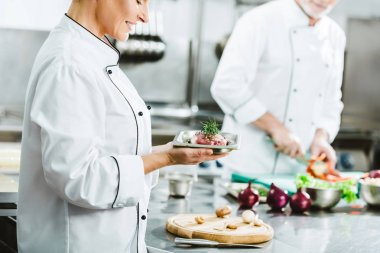 cropped view of female chef in uniform holding meat dish on plate with colleague cooking on background in restaurant kitchen