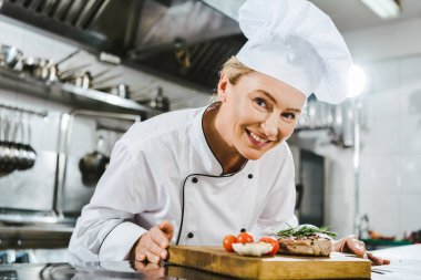 beautiful female chef in uniform holding meat steak with rosemary on wooden board in restaurant kitchen
