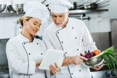 female and male chefs in iniforms using digital tablet during cooking in restaurant kitchen