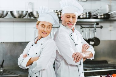 smiling chefs in uniform with arms crossed at restaurant kitchen