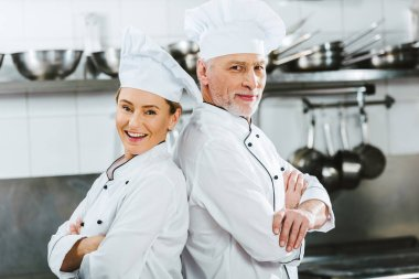 female and male chefs in uniform with arms crossed looking at camera at restaurant kitchen