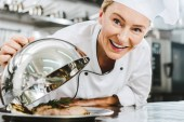 Fotografie beautiful female chef in uniform looking at camera and holding dome from serving tray with meat dish in restaurant kitchen