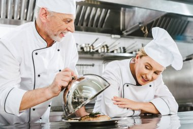 male chef in uniform presenting meat dish on serving tray to female cook in restaurant kitchen