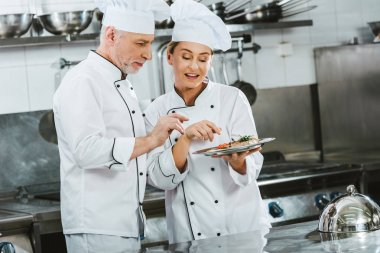 female and male chefs in uniform with meat steak on plate in restaurant kitchen