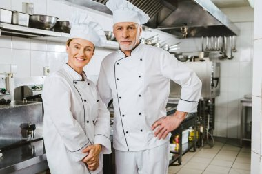 Female and male chefs in uniform looking at camera and smiling at restaurant kitchen stock vector