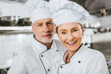 female and male chefs in uniforms looking at camera and smiling at restaurant kitchen