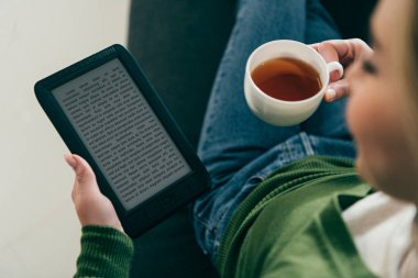 selective focus of woman holding ebook and cup with tea in hands
