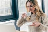 attraktive Frau lächelt, während sie Tasse mit Tee in der Hand hält