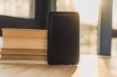 eBook s prázdnou obrazovkou u papírových knih na dřevěný stůl
