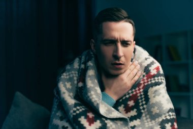 man wrapped in blanket having sore throat at home