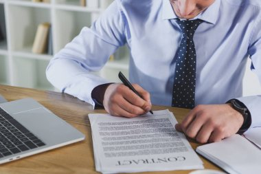 Cropped view of man signing contract on office stock vector