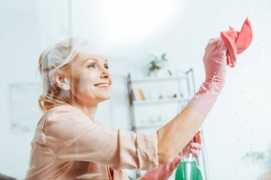 Happy senior woman in rubber gloves cleaning window with rag
