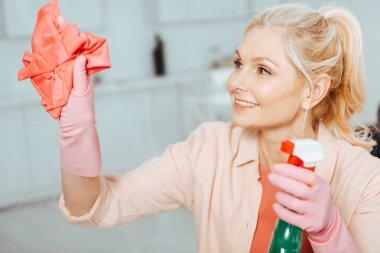Glad senior woman with pony tail cleaning window with spray and rag
