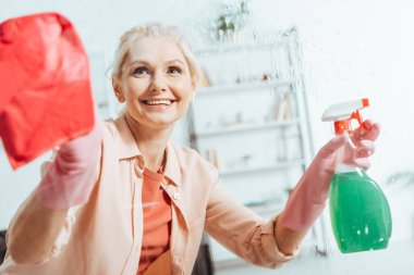 Blissful senior woman in rubber gloves cleaning window