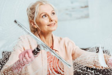 Dreamy senior woman cleaning window with glass wiper