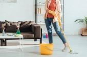 Oříznutý pohled ženy v džínách čištění podlahy s mopem