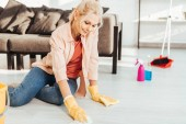 Fotografie Senior woman in yellow rubber gloves cleaning floor with rag