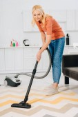 Fotografie Beautiful senior woman cleaning striped carpet with vacuum cleaner