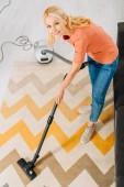 Pohled shora na usmívající se starší žena čištění koberců vysavačem