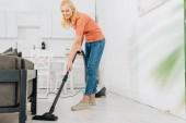 Happy starší žena čištění podlahy s vysavačem
