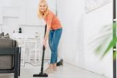 Veselý senior žena čištění podlahy s vysavačem