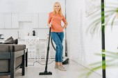 Šťastná starší žena v džínách, být opatrný s vysavačem