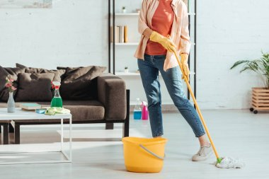 Cropped view of woman in jeans cleaning floor with mop