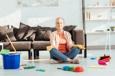 Senior woman sitting in lotus pose during housework