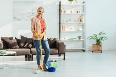 Glad senior woman with mop and bucket posing in living room