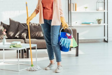 Cropped view of woman in rubber gloves holding mop and bucket with cleaning supplies