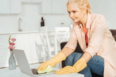 Senior woman in rubber gloves cleaning laptop keyboard