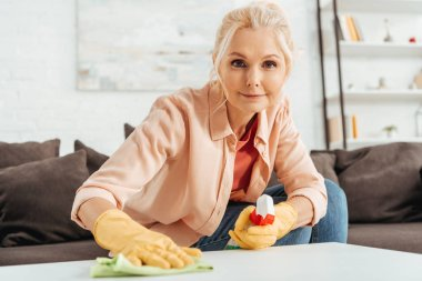 Joyful senior woman in rubber gloves cleaning table surface with rag and spray