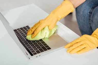 Partial view of woman in yellow rubber gloves cleaning laptop keyboard with rag stock vector