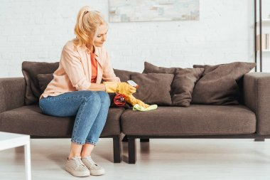 Senior woman in jeans cleaning sofa with spray and rag