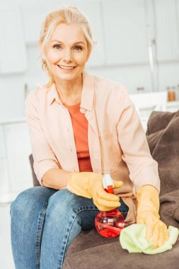 Laughing senior woman in rubber gloves cleaning sofa with spray and rag