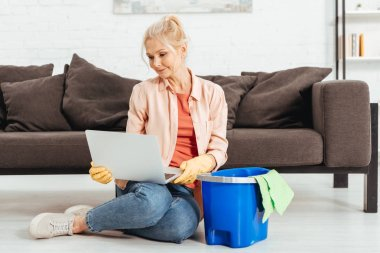 Curious senior woman in rubber gloves posing with laptop while cleaning house