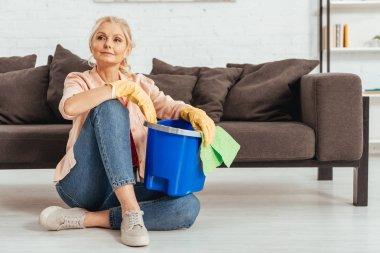 Senior woman sitting on floor with rag and bucket
