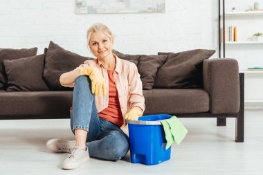 Smiling senior woman posing on floor with bucket and rag