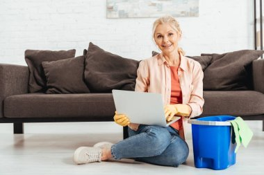 Laughing senior woman in rubber gloves using laptop while cleaning house