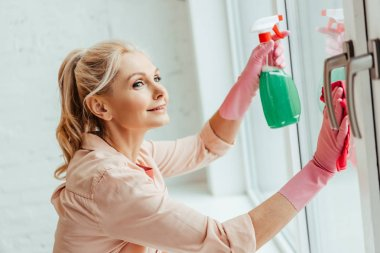 Smiling senior woman in pink gloves cleaning window