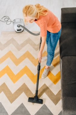 Top view of woman in jeans cleaning carpet with vacuum cleaner