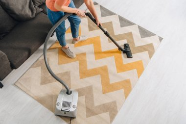 Cropped view of woman cleaning carpet with vacuum cleaner
